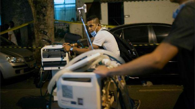 Profissionais de saúde carregam equipamentos para fora do hospital