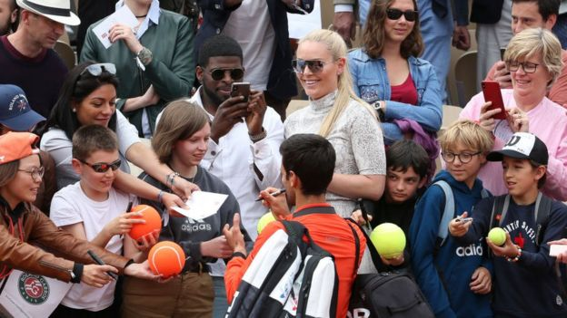 Novak Djokovic firma pelotas ante una multitud.
