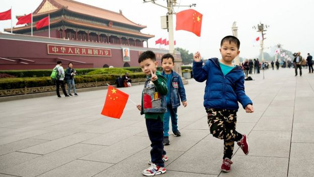 Young boys waves Chinese flags in front of the Tiananmen Gate on October 25, 2018