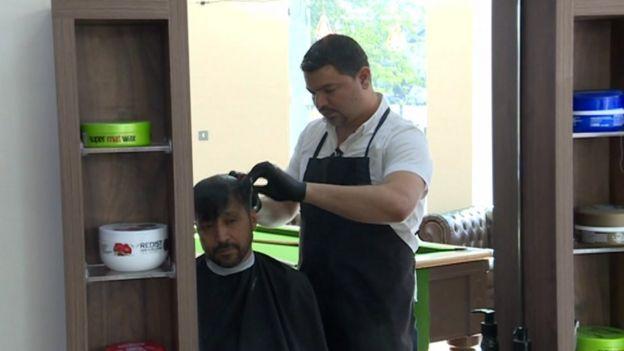 غني يقص شعر أحد الزبائن