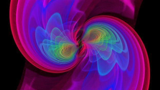 ภาพจำลองที่สร้างขึ้นจากคอมพิวเตอร์ แสดงให้เห็นคลื่นความโน้มถ่วงแผ่ออกมาจากหลุมดำที่กำลังจะรวมตัวกัน