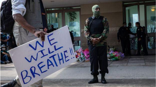 عضو في حركة الفهود السود يقف خارج القاعة عند القاء الناس النظرة الأخيرة على نعش جورج فلويد