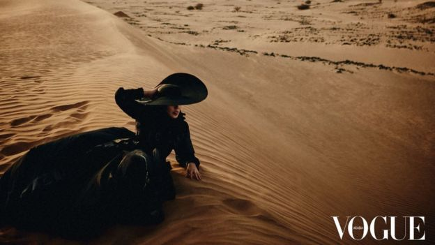 Princess Hayfa Bint Abdullah Al Saud, in a large black hat and dress, lying on a sand dune