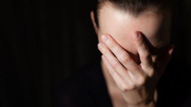 Una mujer tapándose la cara