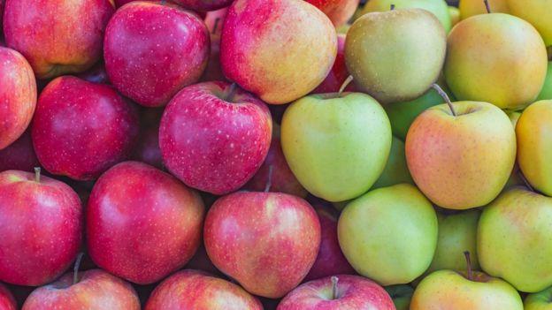 Dezenas de maçãs vermelhas, verdes e amarelas expostas