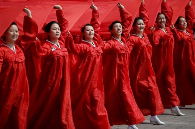 "Attendees carry sheets in the colours of North Korea's national flag during a military parade marking the 105th birth anniversary of country""s founding father Kim Il Sung, in Pyongyang April 15, 2017."