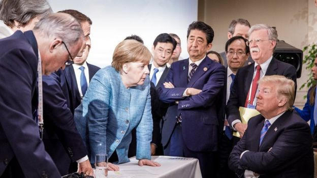 US President Donald Trump talking with German Chancellor Angela Merkel and surrounded by other G7 leaders during a meeting of the G7 summit