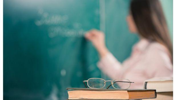 Professora escrevendo em quadro negro numa sala de aula