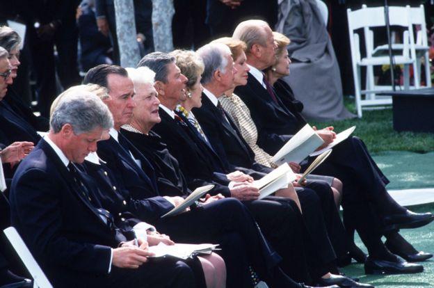 در این عکس بیل و هیلاری کلینتون در کنار جورج بوش پدر و همسرش باربارا هستند و در کنار آنها هم رونالد ریگان و جرالد فورد به همراه همسرانشان در مراسم ترحیم ریچارد نیسکون در سال ۱۹۹۴ کنار هم نشستهاند