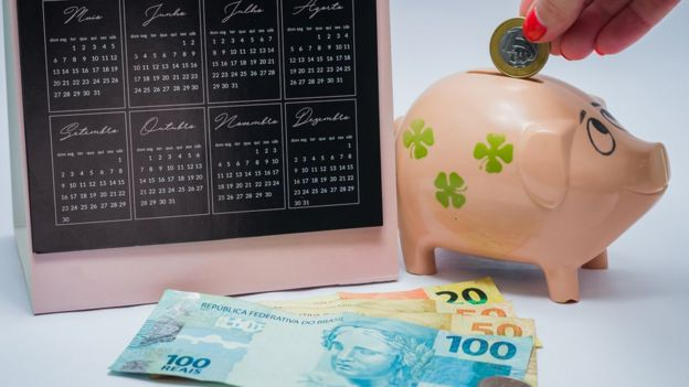 dinheiro e cofrinho ao lado de um calendário