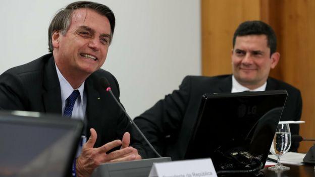 Bolsonaro fala ao microfone ao lado de Moro; ambos sorriem, sentados