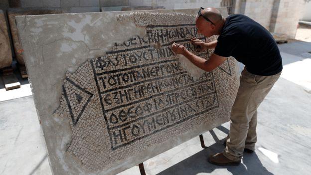 Un arqueólogo limpia un mosaico en griego de hace 1.500 años.