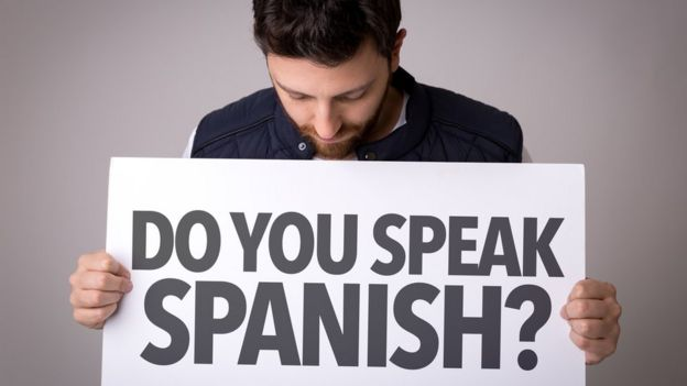 Un hombre sostiene un cartel con la pregunta en ingles: ¿Hablas español?