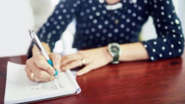 Pessoa escrevendo com caneta em um caderno