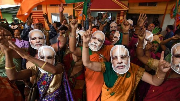 """Indian Bharatiya Janata Party (BJP) supporters wearing masks of Indian Prime Minister Narendra Modi dance as they celebrate on the vote results day for India""""s general election at BJP office in Guwahati on May 23, 2019."""