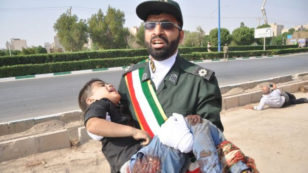 A soldier carries an injured child at the scene of the attack