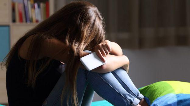 Menina adolescente sentada, com o rosto debruçado nos joelhos e um celular na mão