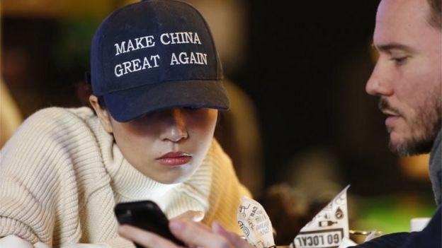 A woman wears a cap with a China message that is reminiscent of the campaign slogan of US President-elect Donald Trump