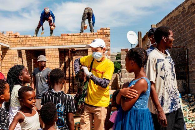 Voluntário distribui sabão em Joanesburgo, na África do Sul