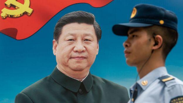 Militar chinês em frente a pôster com imagem de Xi Jinping