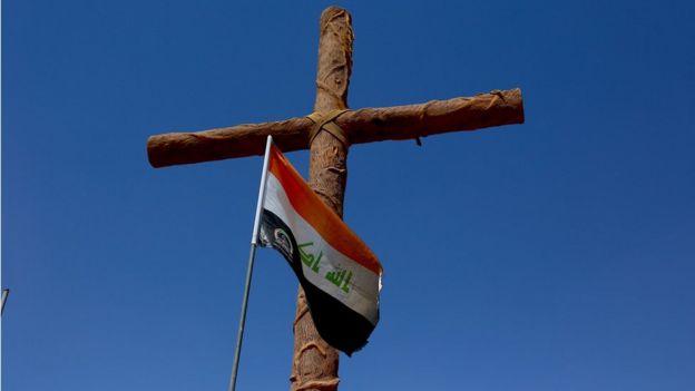 Cross with Iraqi flag at entrance to Christian town of Qaraqosh