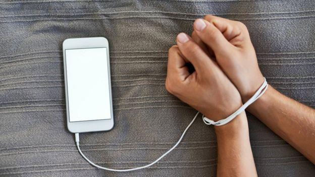 Unas manos atadas con el cable de un teléfono móvil
