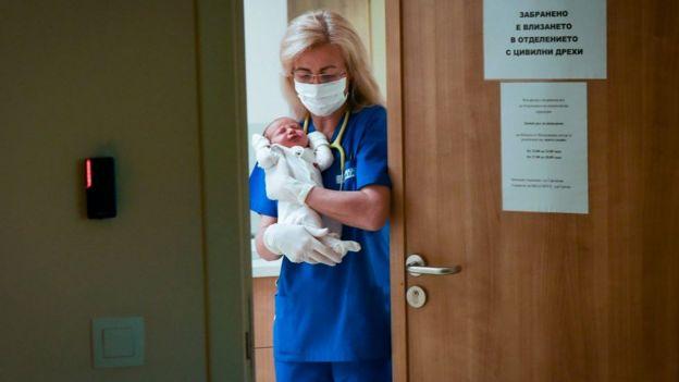 Enfermeira segura bebê em hospital na Bulgária