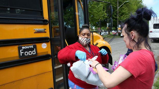 Una mujer le entrega alimentos a otra en Seattle, Washington