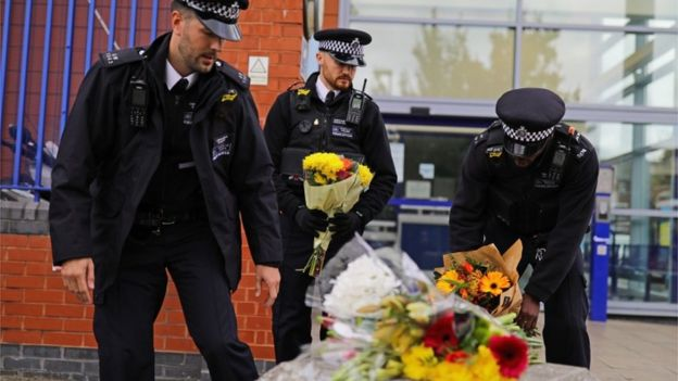 Police officers leave flowers outside Croydon Custody Centre in south London