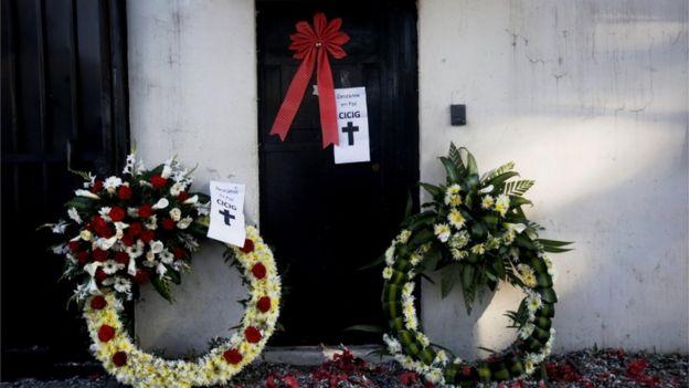 """Coronas de flores y carteles con la leyenda """"Cicig descanse en paz""""."""