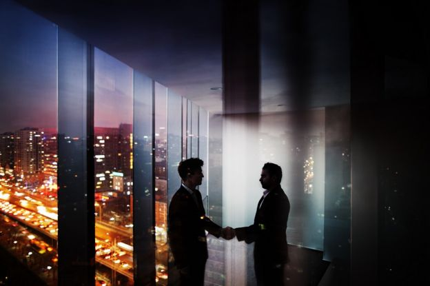 Two shadowy figures shake hands in a skyscraper