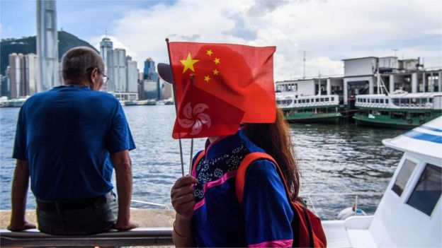 A woman holds Chinese and Hong Kong flags as she gets off a boat in Victoria Harbour on 1 July 2020