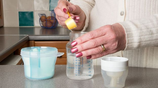 Mujer preparando tetero.