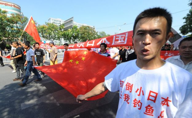Chinese demonstraters hold banners as they march past the Japanese embassy during a protest over the Diaoyu islands issue, known as the Senkaku islands in Japanese, in Beijing on September 16, 2012.