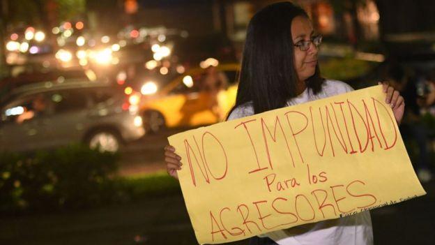 """Una mujer protesta en El Salvador con una pancarta que dice """"No impunidad para los agresores""""."""