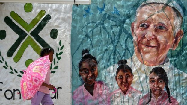 Niña pasa frente a un mural con la cara del papa Francisco en Cartagena de Indias, Colombia.