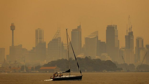 Smoke haze from bushfires turns the sky orange and obscures buildings in Sydney's skyline
