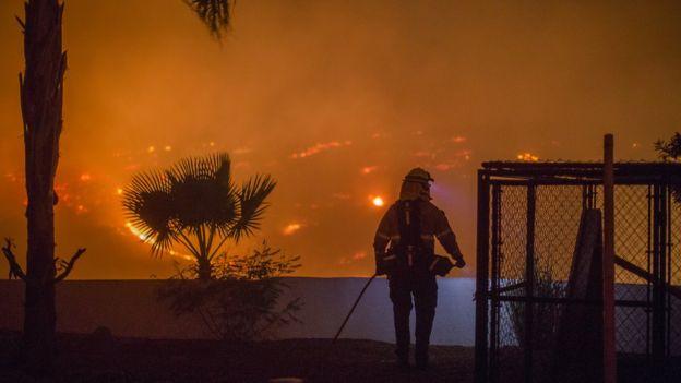 Bombero observa el panorama de uno de los incendios en el sur de California