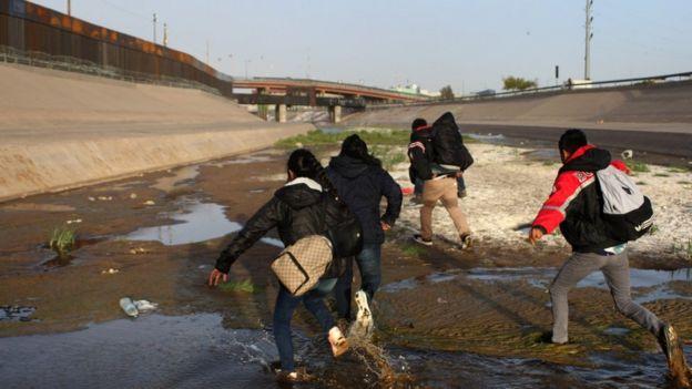 Un grupo de personas corre en el Río Bravo, en el punto de control del Paso del Norte, en Ciudad Juárez.