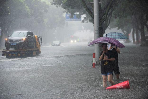 Warga memegang payung berusaha menyeberang jalan melalui banjir di tengah hujan lebat setelah topan dahsyat Lekima mendarat di Ningbo.
