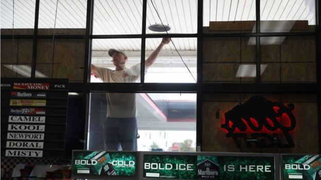 Wesley Jacobs measures a space for plywood as he helps board up the windows on a business before the possible arrival of Hurricane Laura on August 25, 2020