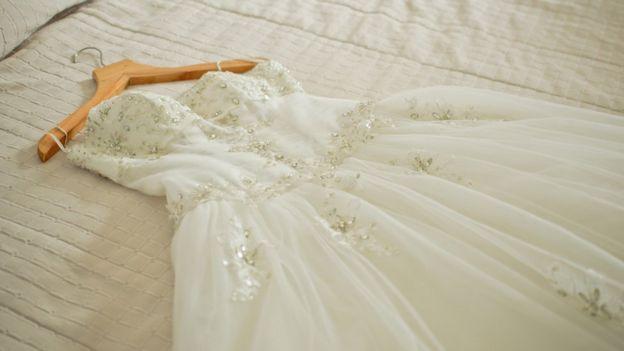 A wedding dress on a bed
