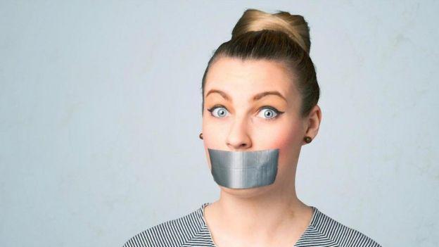 Una mujer con la boca tapada
