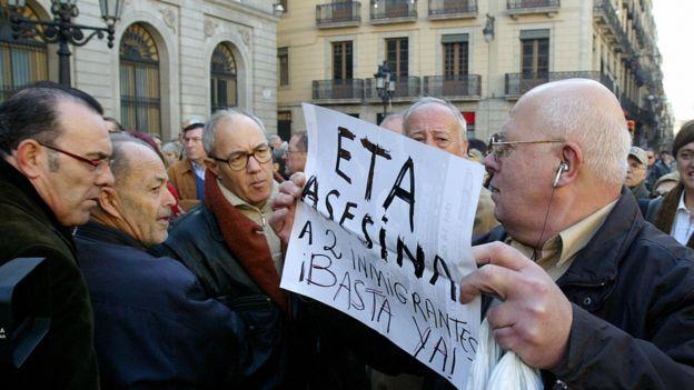 "Manifestante con cartel que dice ""ETA asesina inmigrantes, !Basta ya!"""