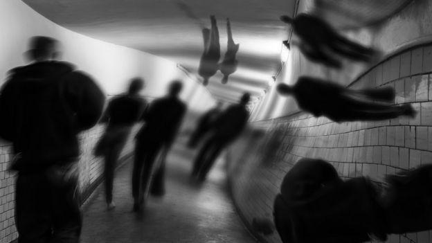 imagen en blanco y negro de personas caminando por un pasillo