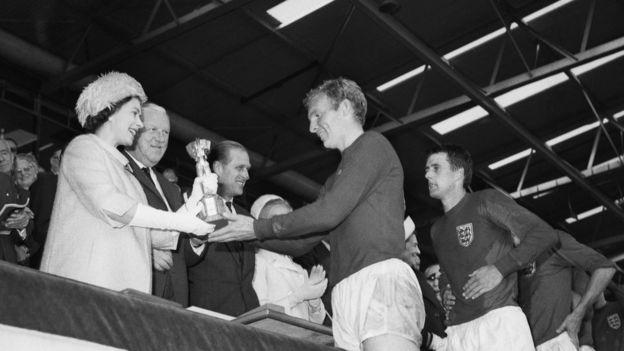英格蘭隊隊長鮑比·摩爾(Bobby Moore)從英女王伊麗莎白二世手中接過世界杯冠軍獎杯。