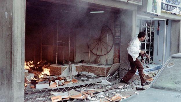 Um homem com um par de sapatos na mão sai de uma loja destruída em 27 de fevereiro de 1989, durante onda de protestos contra aumento do custo de vida na Venezuela motivada principalmente pela alta de preços da gasolina