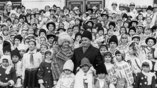 Romanian communist leader Nicolae Ceausescu pictured in around 1985 with his wife Elena and a large group of children in national costume.