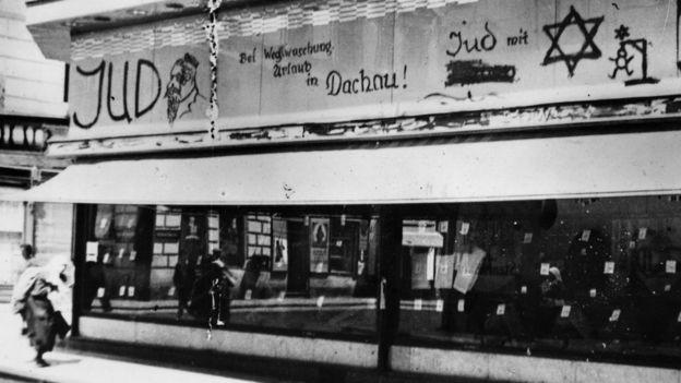 """Магазин еврейского портного с антисемитским граффити, """"Кто сотрет, тот будет отдыхать в Дахау!"""" Вена, 1938 год."""