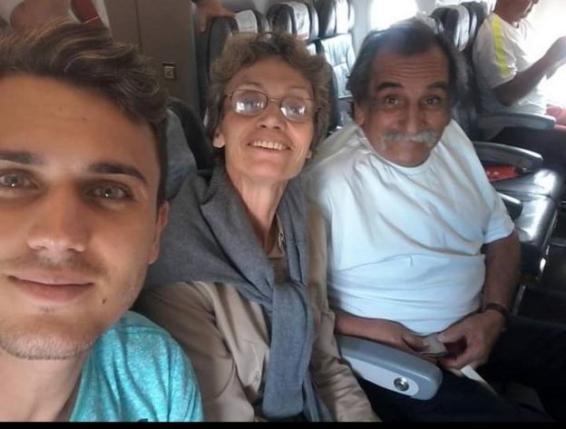 Imagem mostra Pedro Giles, de 24 anos, a mãe, Sueli, e o pai, o músico Lúcio Yanel sentados em poltronas de avião. Sueli tem Alzheimer e o marido faz serenatas para ela todos os dias